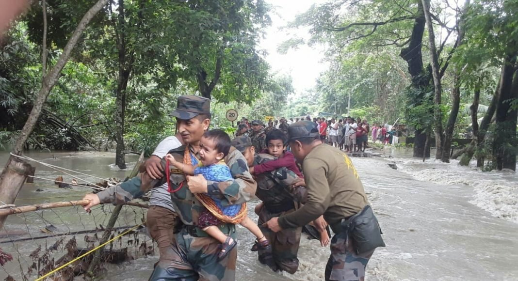 Army soldiers evacuate a baby from flooded areas. Photo courtesy: AIR News Guwahati