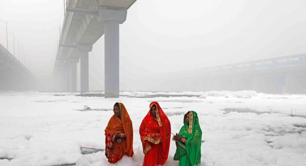 Devotees stand in knee-deep toxic foam in Yamuna river during Chatth Puja in Delhi